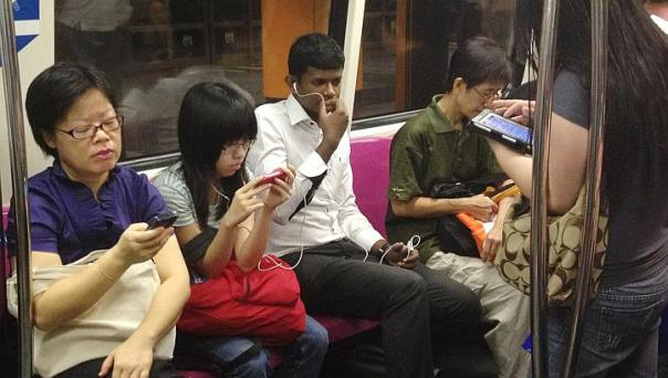 People using phones on the MRT - not an unfamiliar sight in Singapore